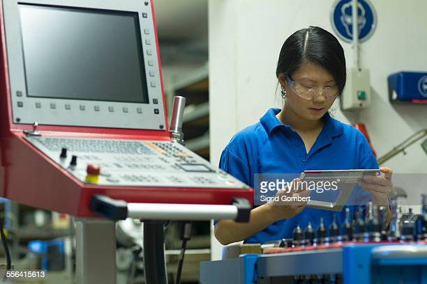 young woman holding measuring equipment in industrial workshop - sigrid gombert stock-fotos und bilder