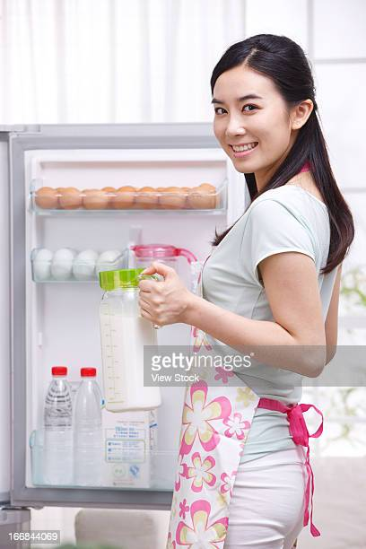 Young woman holding milk in kitchen