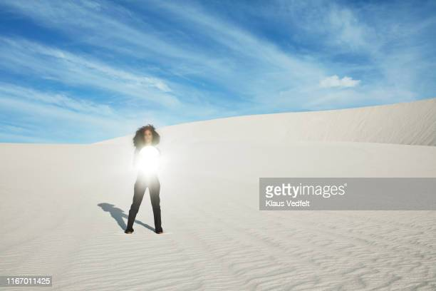 young woman holding mirror while standing on white sand at desert - junge frau rätsel stock-fotos und bilder