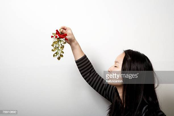 young woman holding mistletoe, eyes closed - mistletoe stock photos and pictures