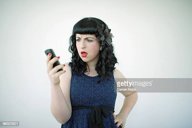 Young woman holding mobile looking shocked