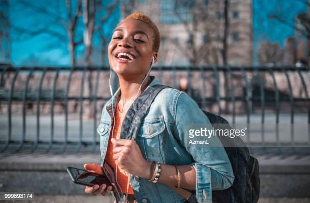 jovem, segurando o telefone celular e ouvir música - cabelo curto comprimento de cabelo - fotografias e filmes do acervo
