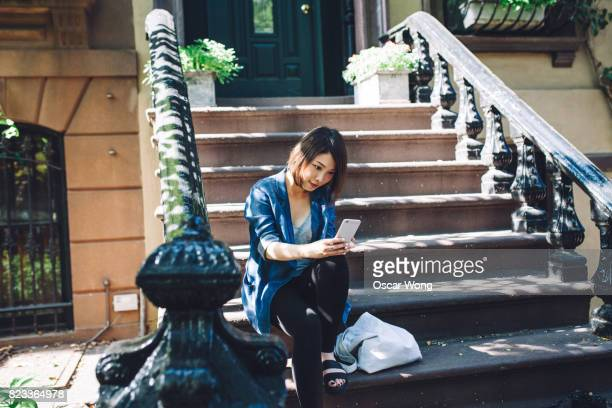 Young woman holding mobile phone and sitting on steps outside a residential building