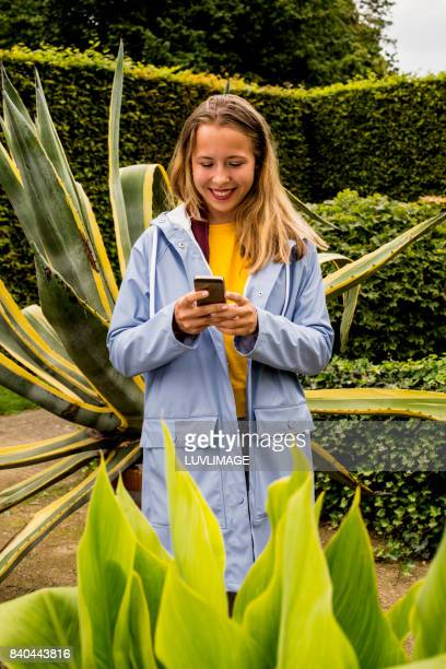 Young woman holding mobile phone in the parc.