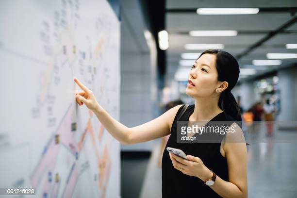 young woman holding mobile phone looking at city map in subway station - u bahnstation stock-fotos und bilder