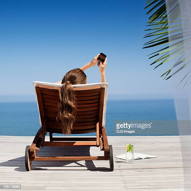 Young woman holding mobile phone near pool