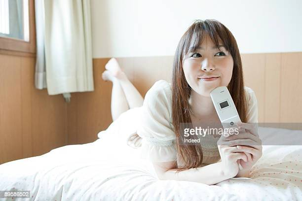 Young woman holding mobile phone on bed