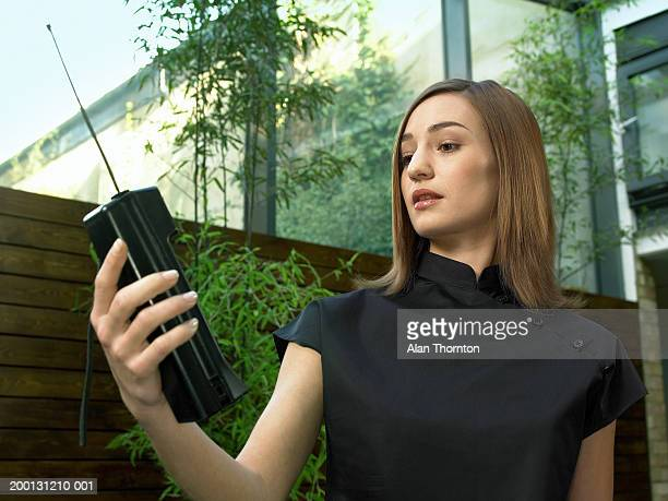 Young woman holding mobile phone, outdoors