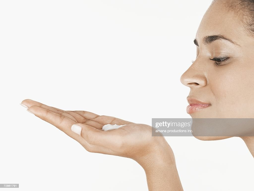 Young woman holding moisturizing cream on palm of hand : Stock Photo