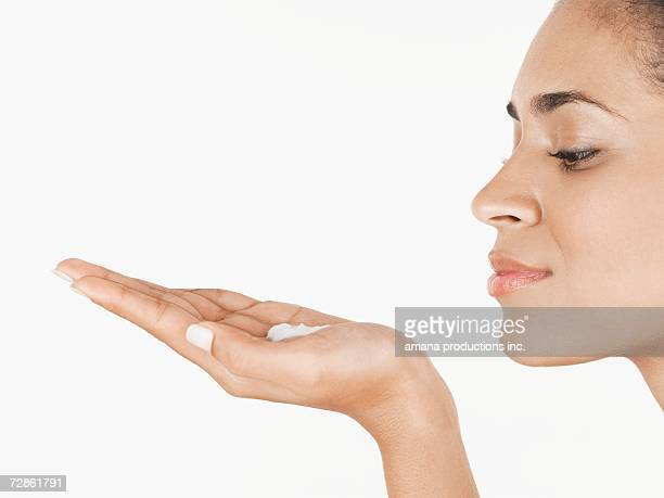Young woman holding moisturizing cream on palm of hand
