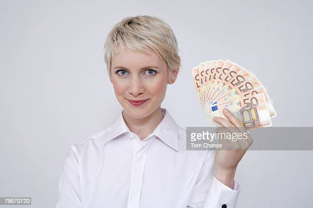 young woman holding money, portrait - blouse stock pictures, royalty-free photos & images