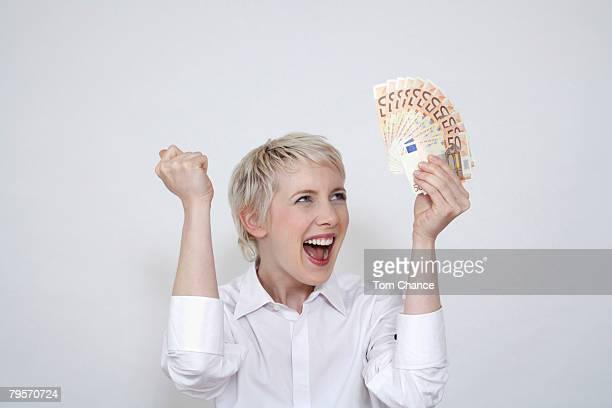 'Young woman holding money, portrait'