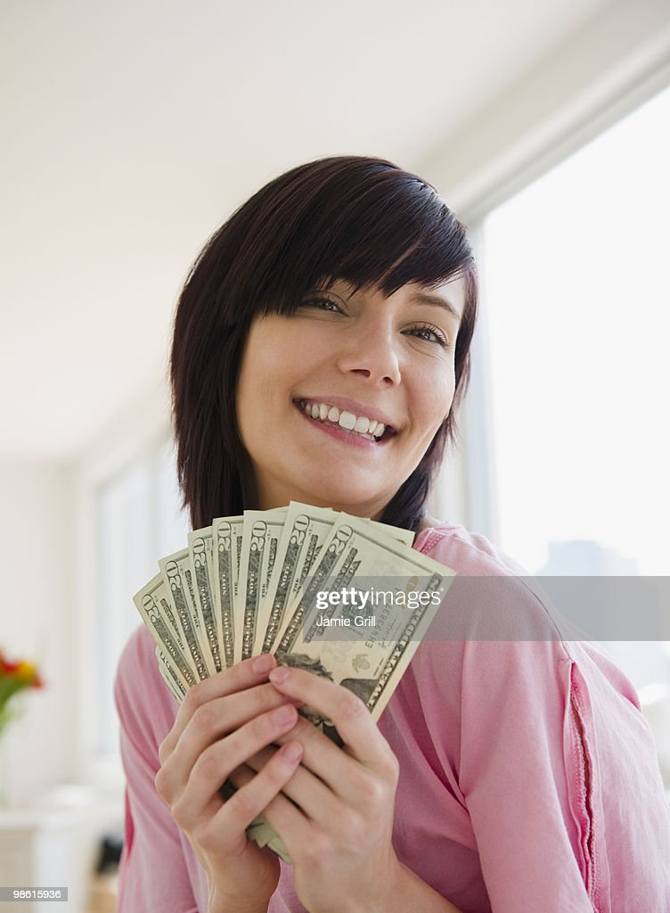 Young woman holding money, smiling : Stock Photo