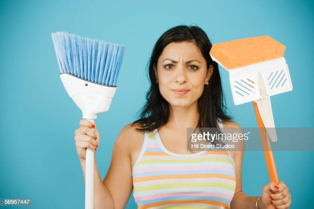 Young woman holding mop and broom