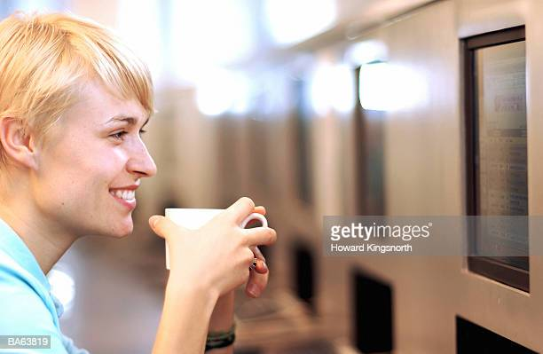 Young woman holding mug and using computer in internet cafe, close-up