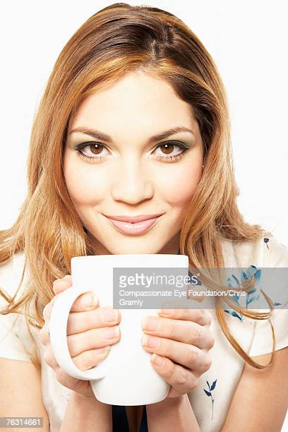 "young woman holding mug, portrait, head and shoulders - ""compassionate eye"" stock-fotos und bilder"