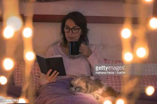 young woman holding mug reading book while sitting on bed at home - one animal stock pictures, royalty-free photos & images