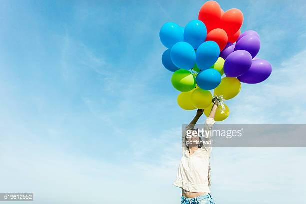Young woman holding multi colored hot air balloons