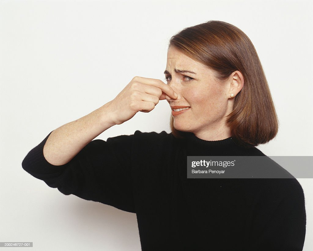 Young woman holding nose : Stock Photo