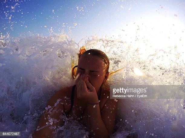 Young Woman Holding Nose While Swimming In Sea