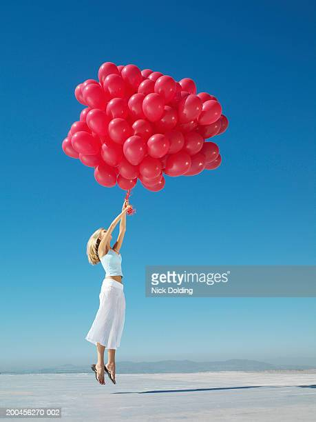 young woman holding on to large bunch of red balloons - leichter stock-fotos und bilder