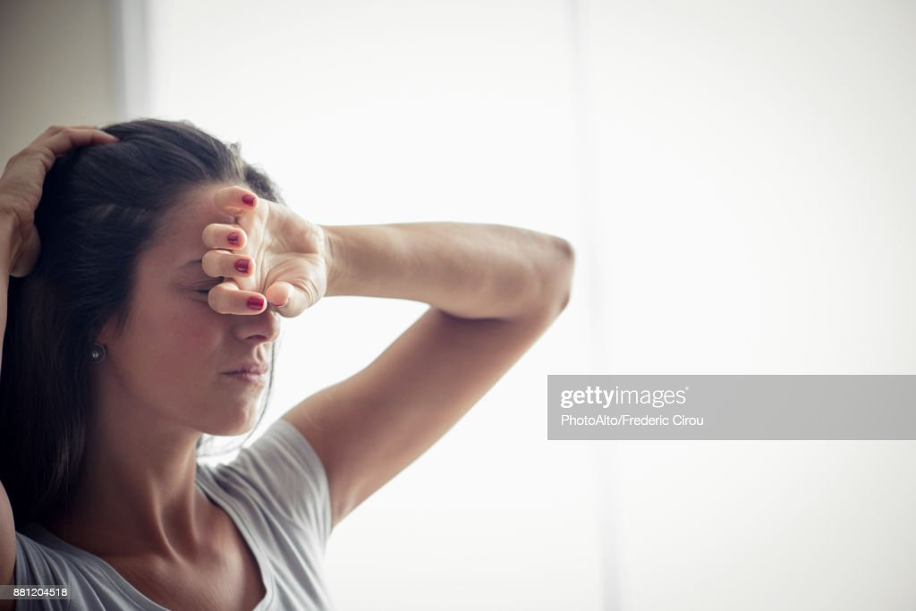 Young woman holding one hand on forehead : Stock Photo
