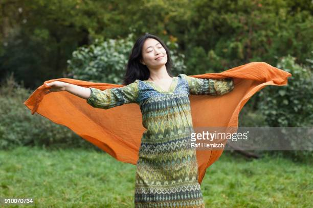 Young woman holding orange scarf while standing with arms outstretched against trees at park
