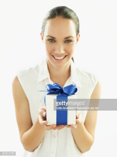 Young woman holding out a present