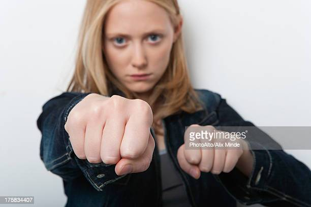 Young woman holding out clenched fists