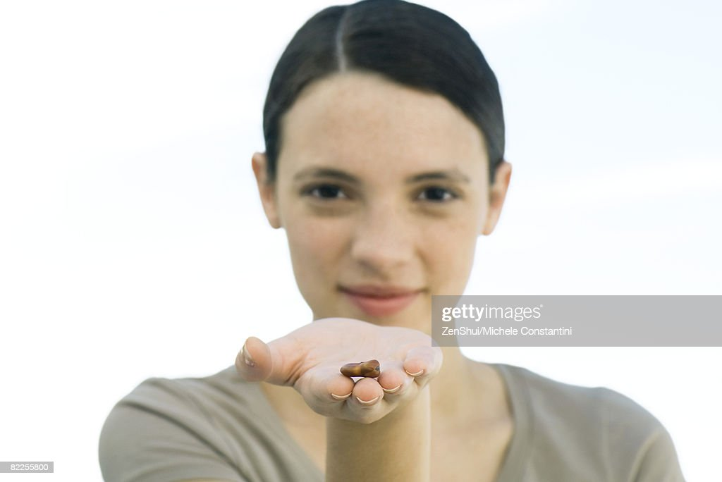 Young woman holding out dried bean in palm of hand : Stock Photo