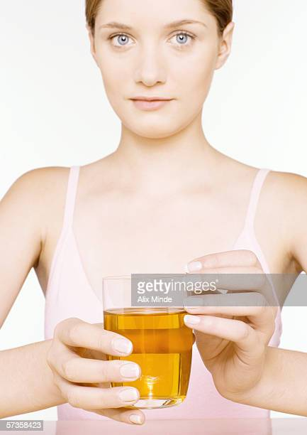 Young woman holding out glass of apple juice