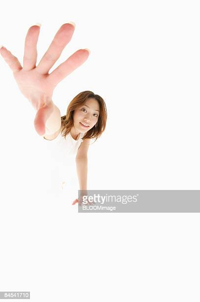 Young woman holding out hand, studio shot