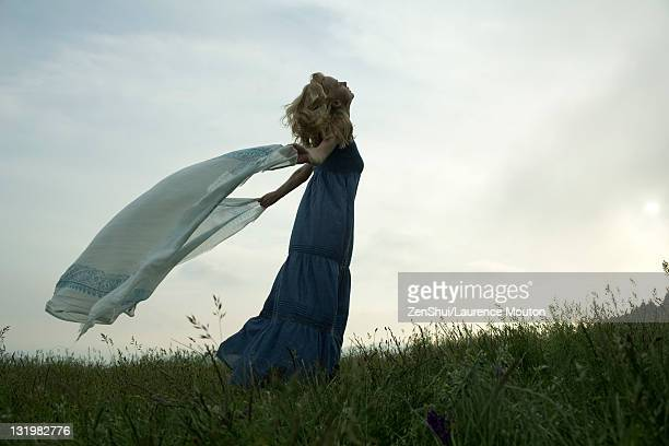young woman holding out scarf in breeze - long dress stock pictures, royalty-free photos & images