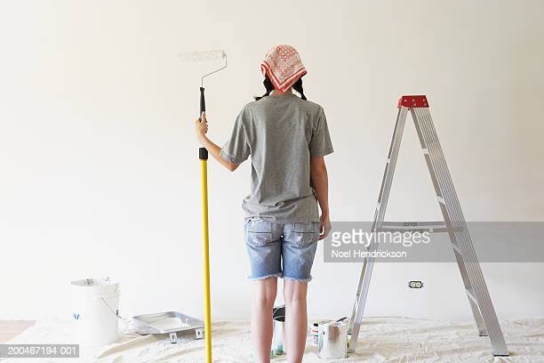 young woman holding paint roller, rear view - paint roller stock pictures, royalty-free photos & images