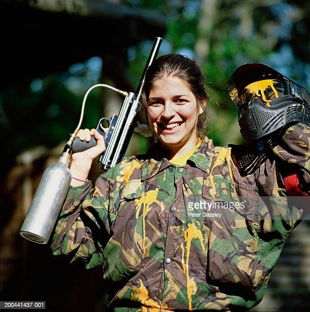 Young woman holding paintball gun and helmet, smiling, portrait