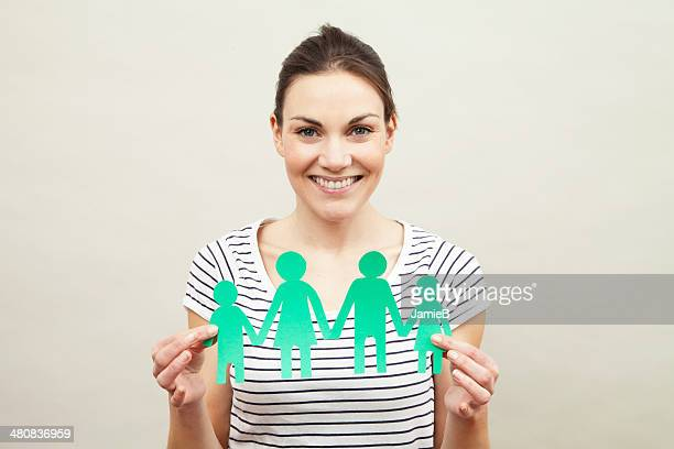 Young woman holding paper chain family