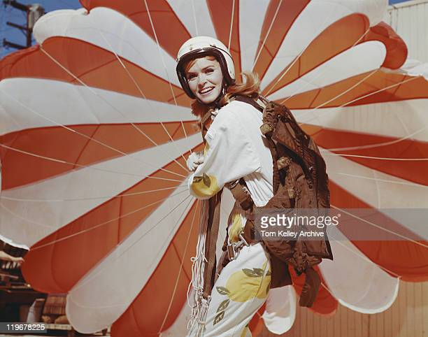 Young woman holding parachute, smiling, portrait