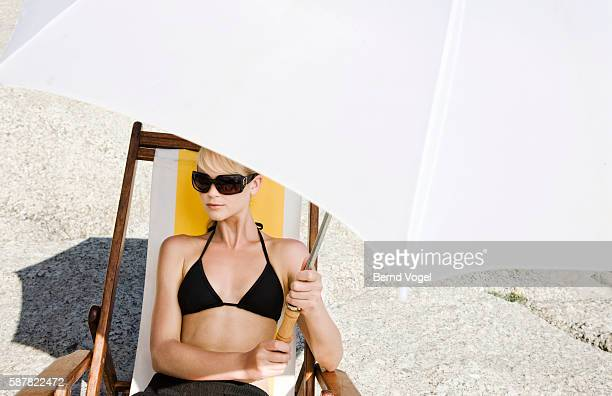 young woman holding parasol while sunbathing - parasol stock pictures, royalty-free photos & images