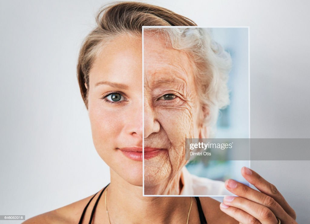 Young woman holding picture of elderly woman : Stock Photo