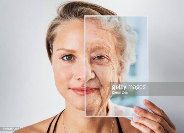 Young woman holding picture of elderly woman