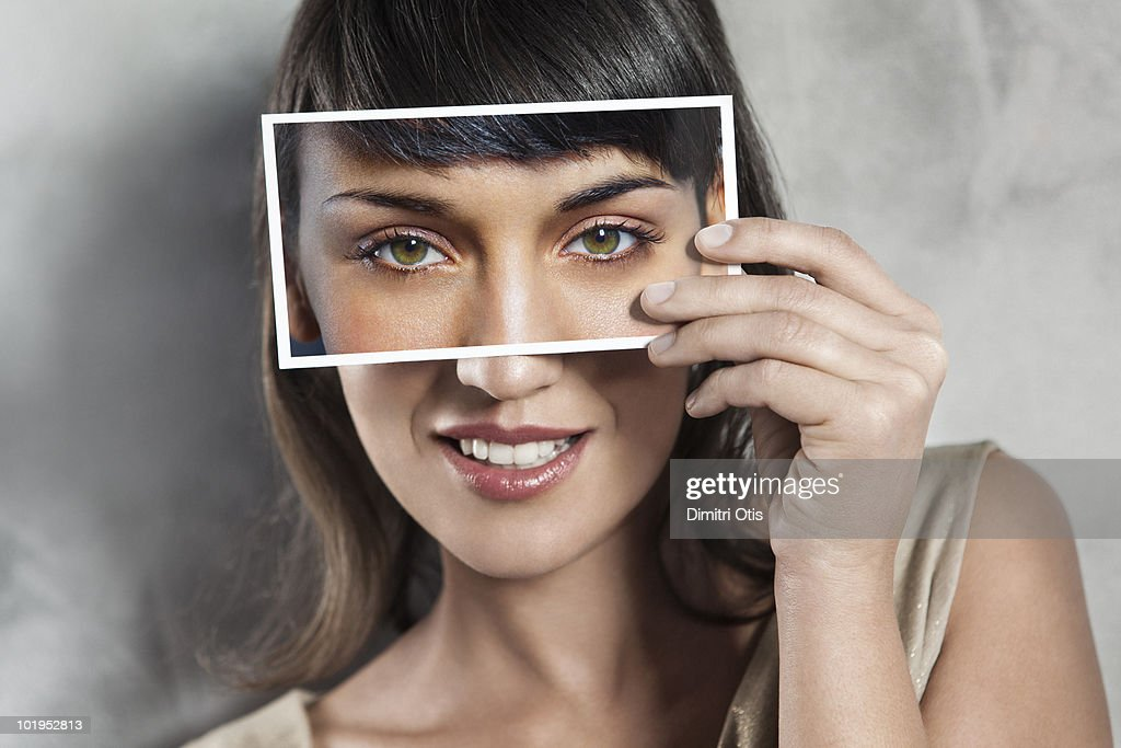 Young woman holding picture of her own eyes : Stock Photo