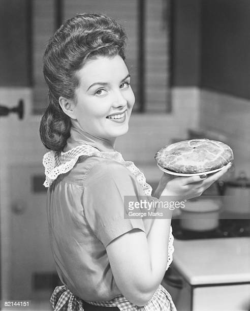 Young woman holding pie, (B&W), portrait
