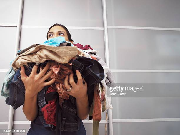 young woman holding pile of laundry, low angle view - laundry stock pictures, royalty-free photos & images