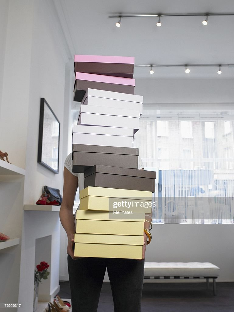 Young woman holding pile of shoe boxes obscuring face : Stock Photo