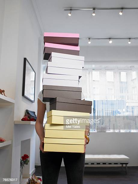 Young woman holding pile of shoe boxes obscuring face