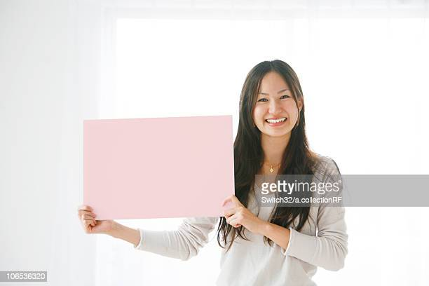 Young Woman Holding Pink Rectangle