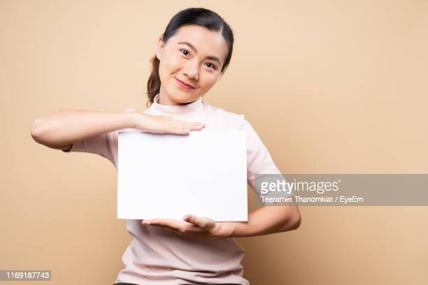 young woman holding placard against beige background - placard stock pictures, royalty-free photos & images