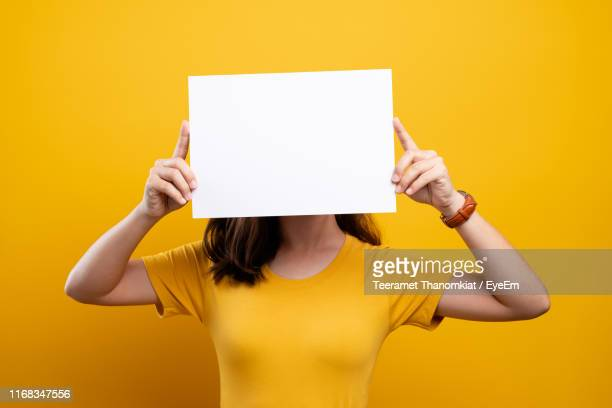 young woman holding placard against yellow background - obscured face stock pictures, royalty-free photos & images