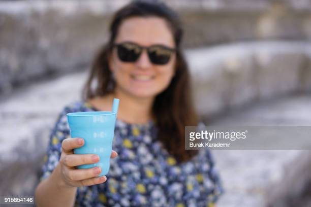 Young woman holding plastic blue glass