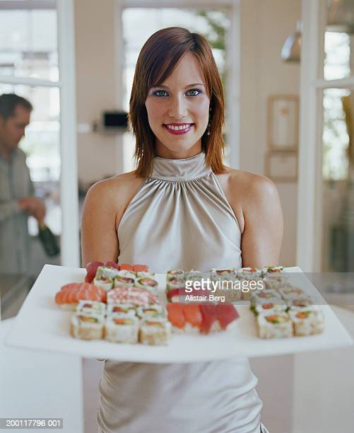 Young woman holding plate of sushi, portrait